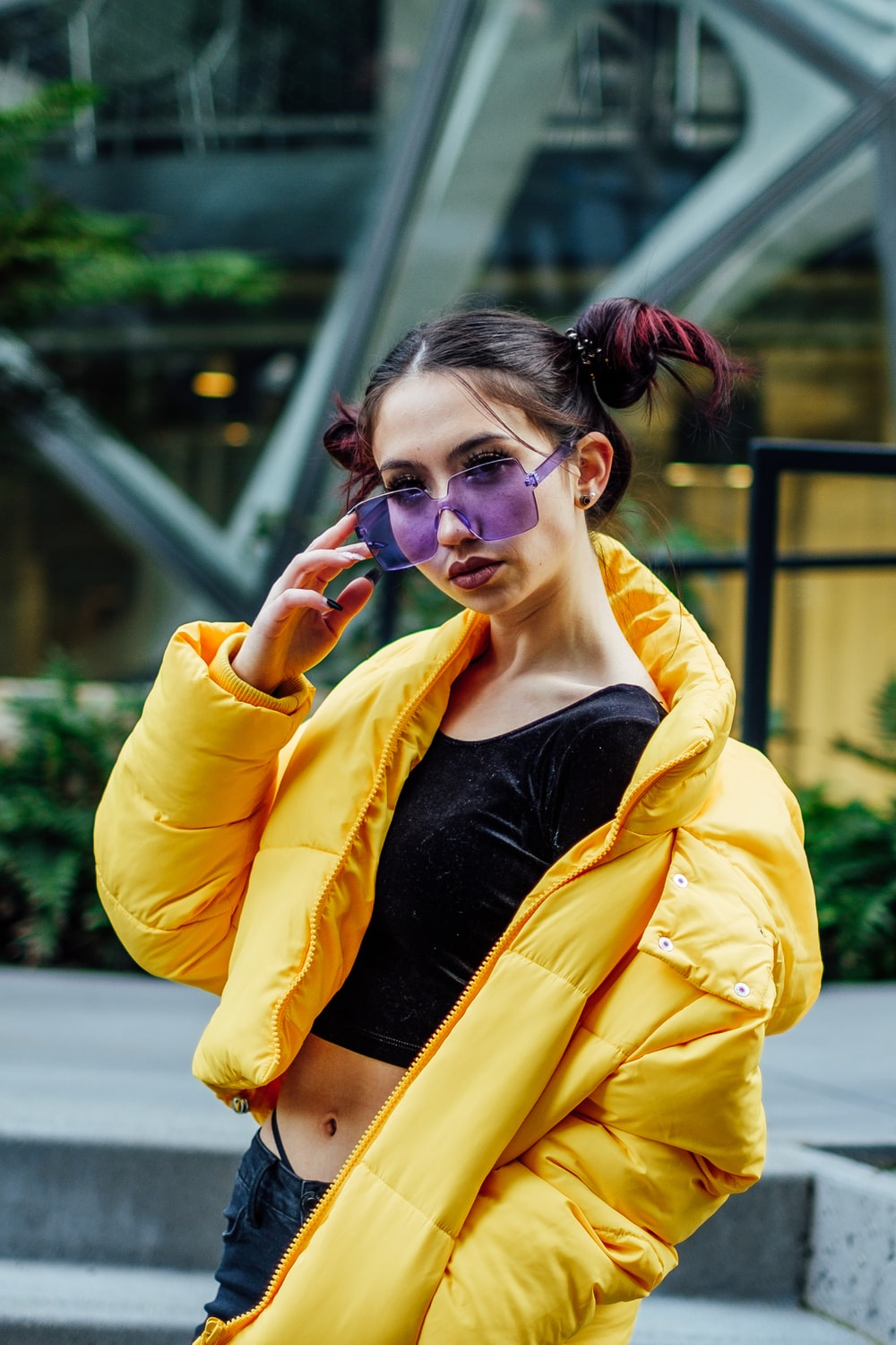 woman in yellow jacket with black inner shirt wearing purple sunglasses during daytime
