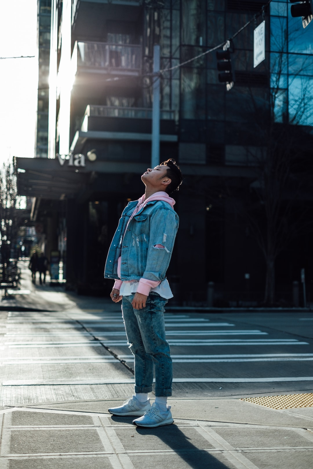 man in blue denim jacket standing on road during daytime