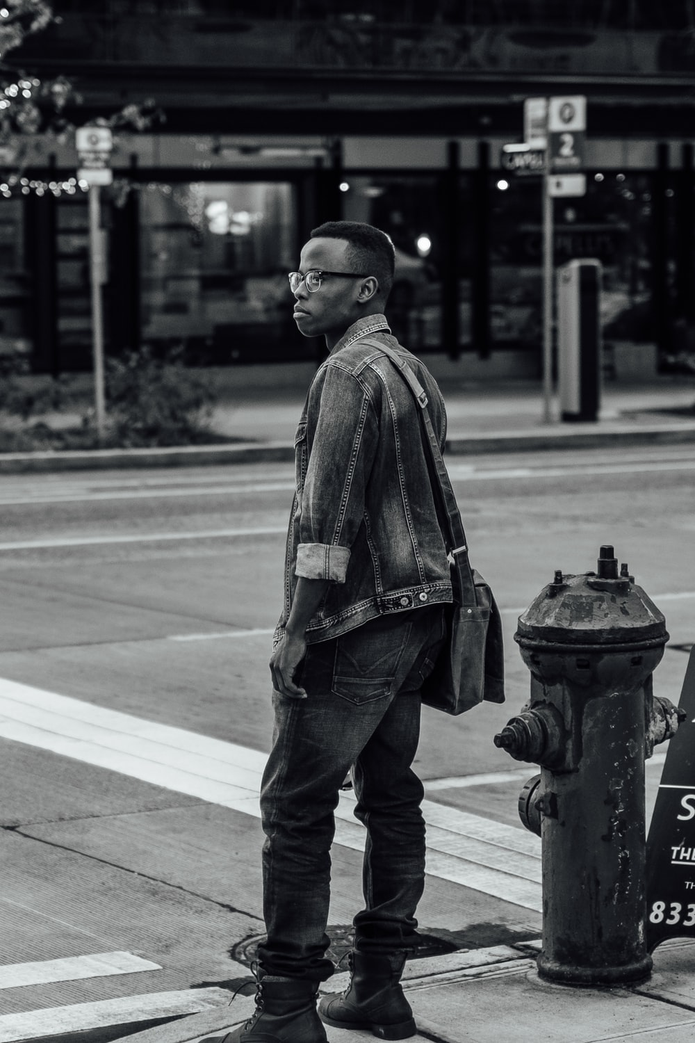 greyscale photo of man in jacket and denim jeans standing beside road