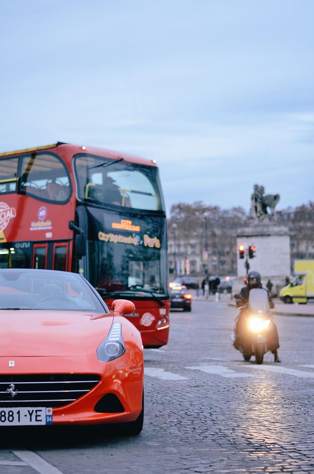 red car beside bus near statue