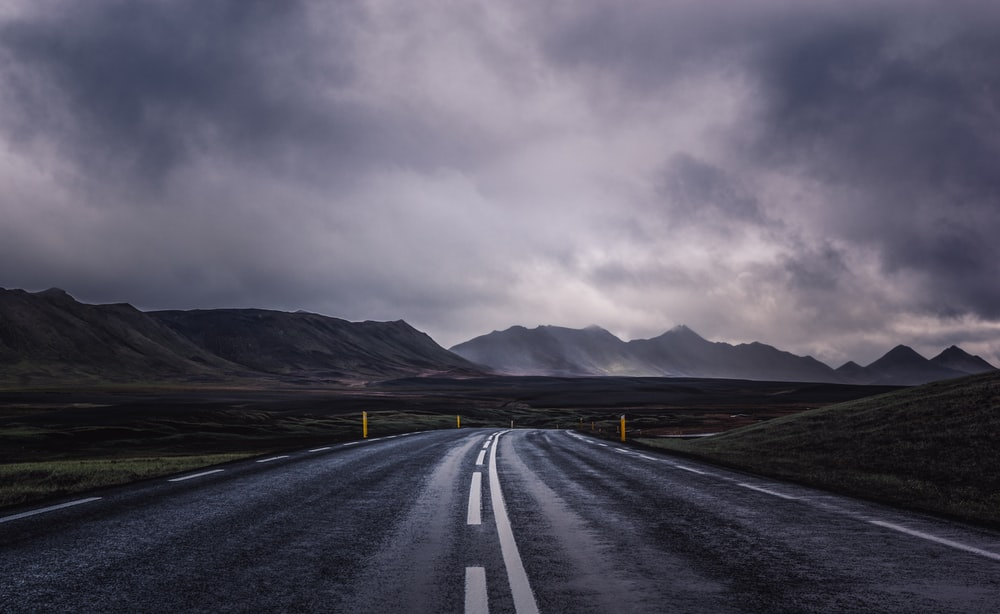 curved asphalt road during cloudy daytime