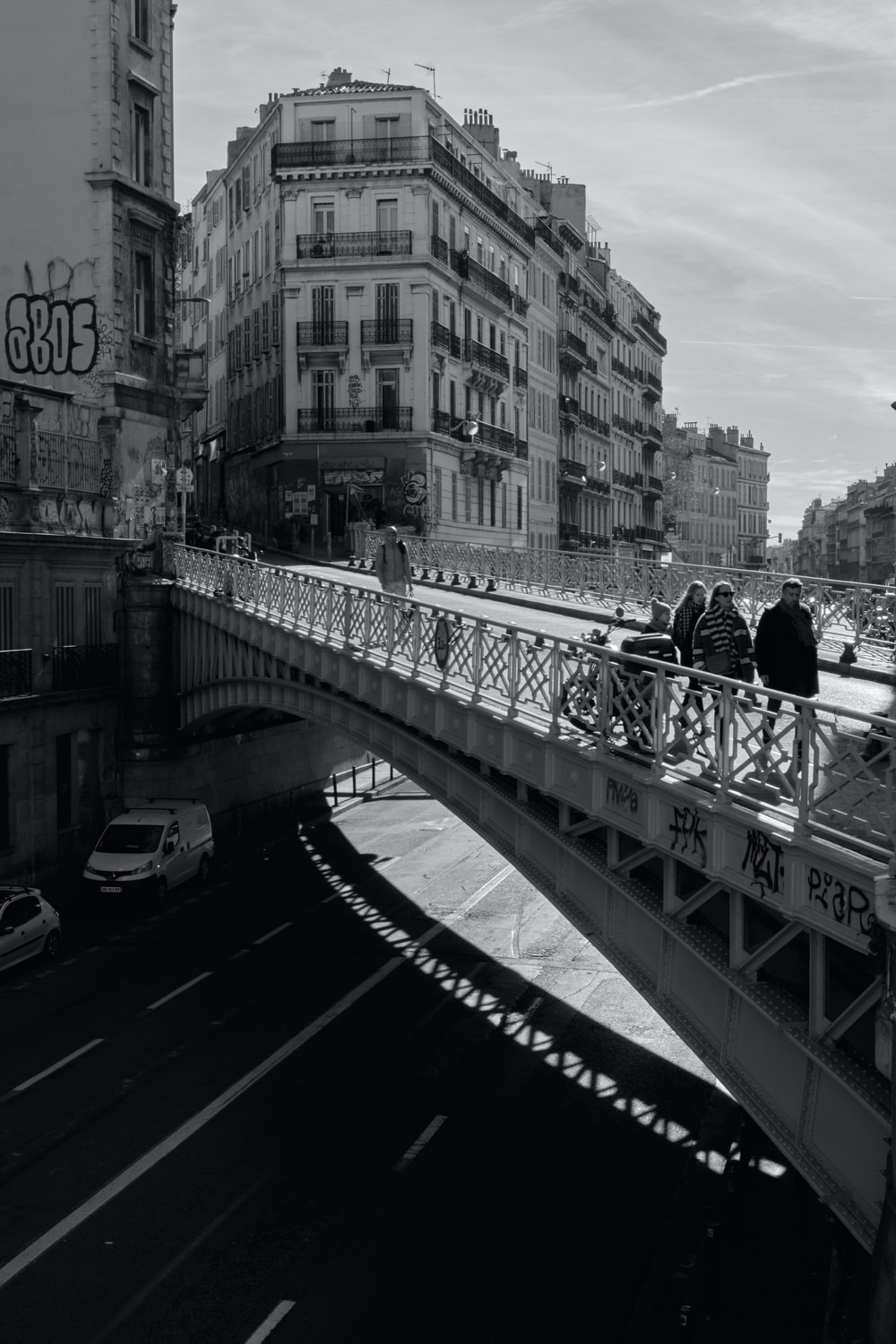 greyscale photo of people walking on bridge