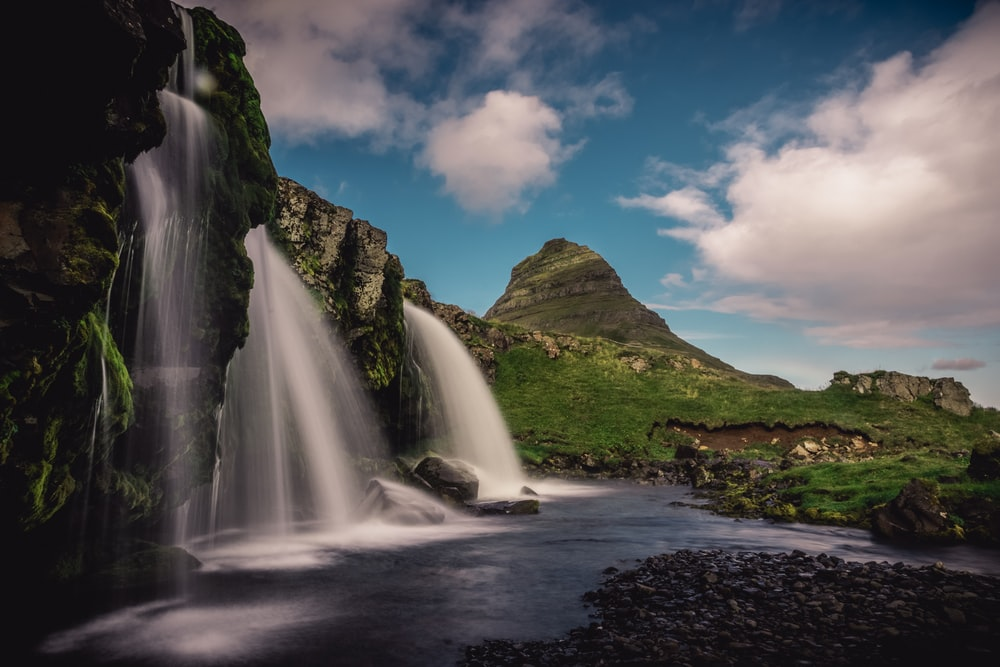time-lapse photography of waterfalls near mountain during daytime