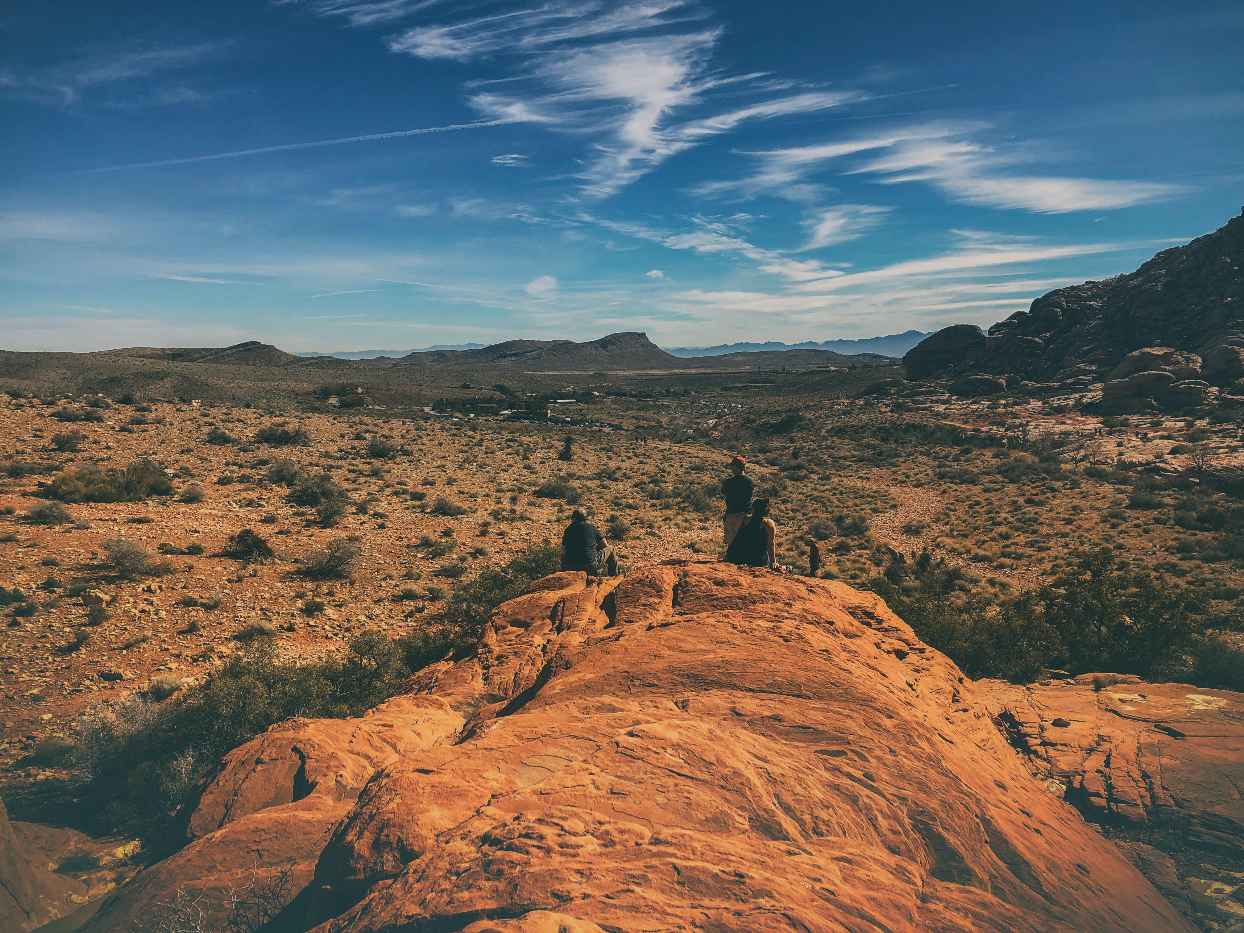 three men standing on rock formation