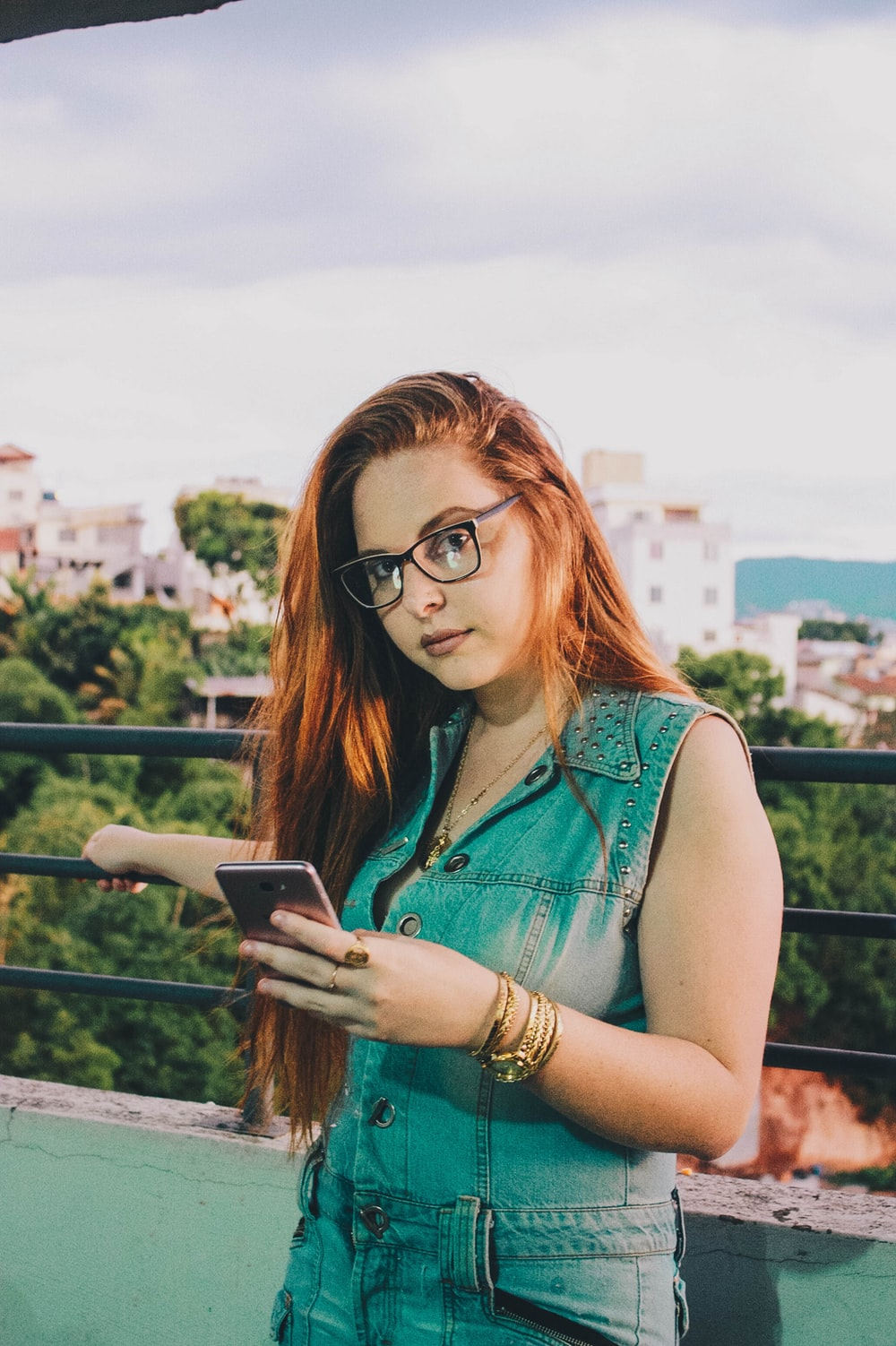 woman in blue denim sleeveless button-up tops using smartphone