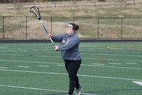 woman wearing gray jacket standing and holding lacrosse stick on green field at daytime