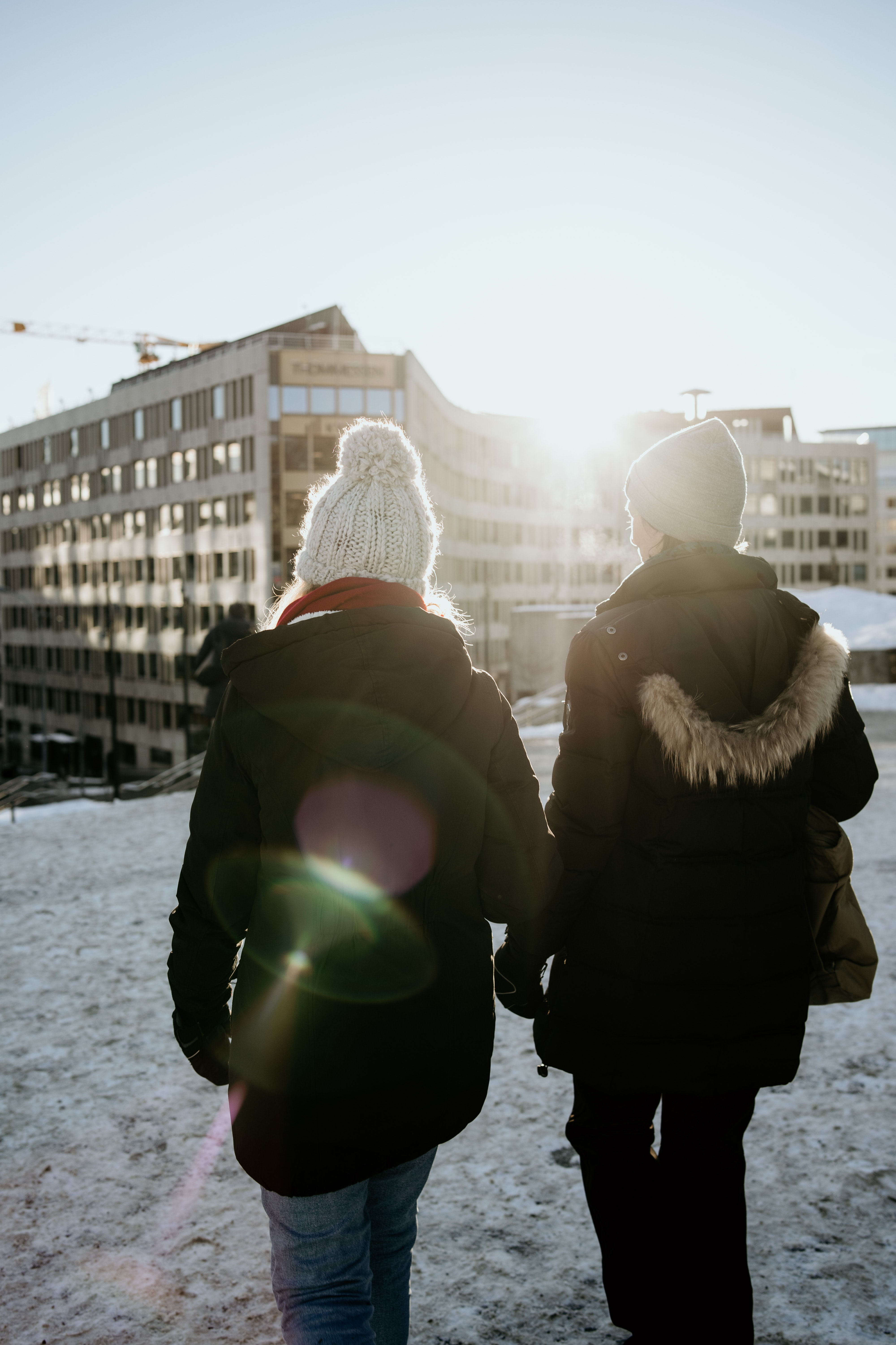 two person wearing jacket walking on snow covered field during daytime