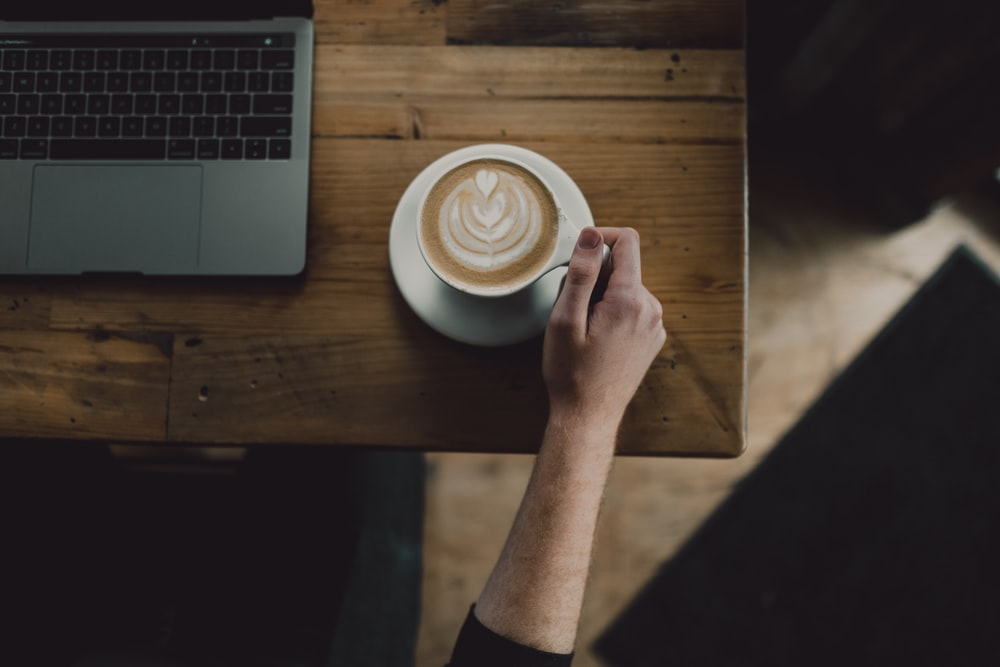 person holding cup of coffee on table beside laptop computer