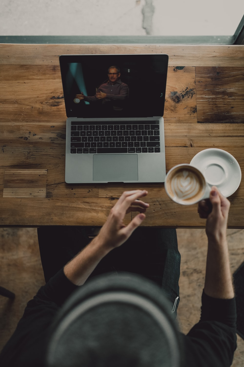 person holding cup of latte while facing MacBook Pro