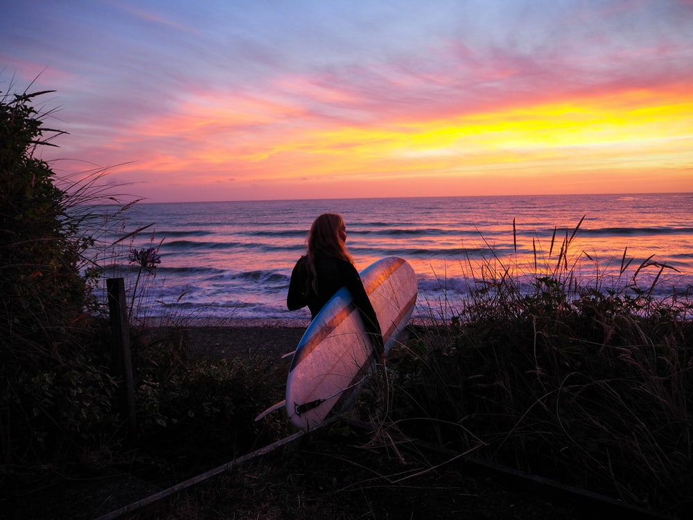 woman holding surfboard front of the sea during golden hour
