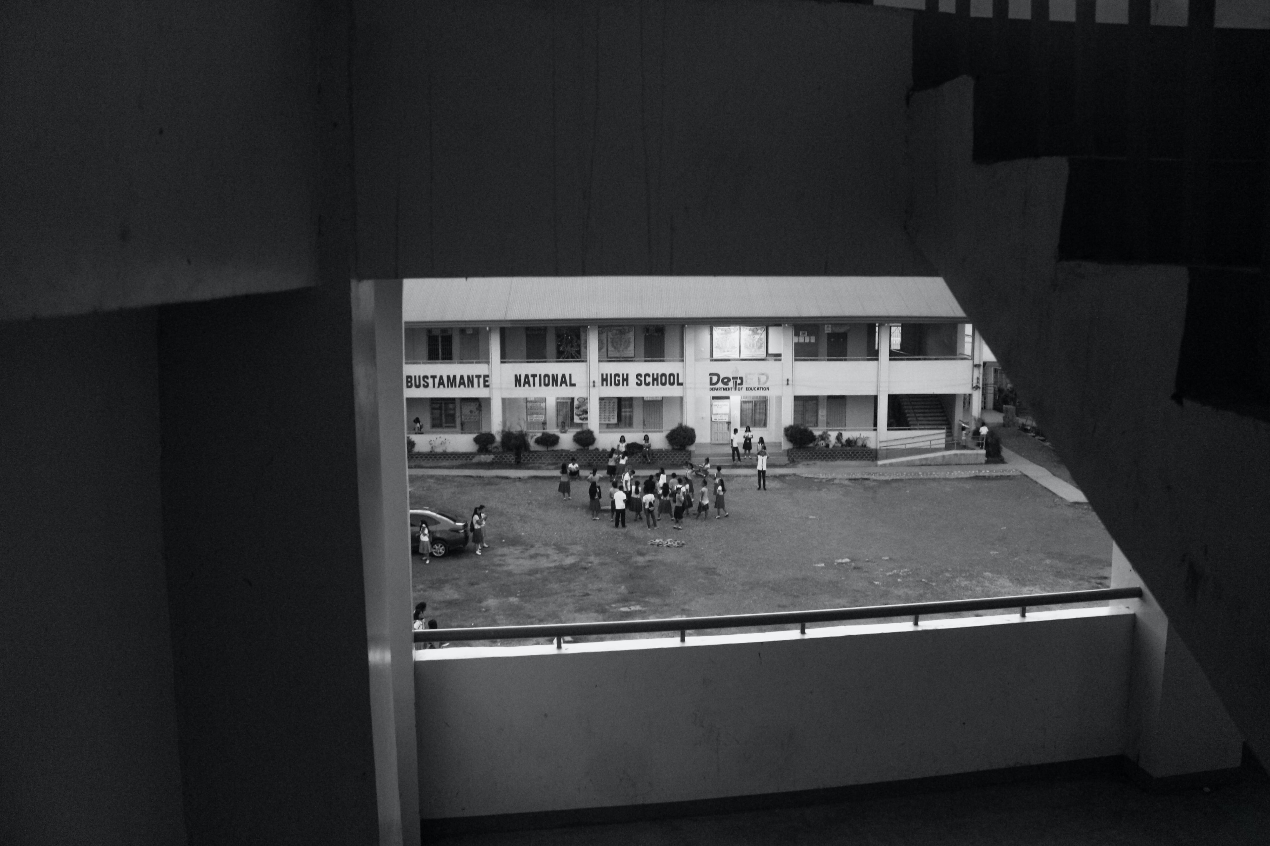 grayscale photography of people standing front of building