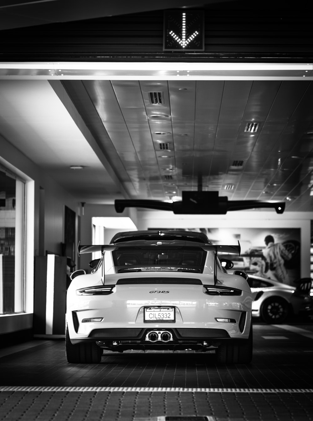 grayscale photo of sports car parked in parking lot