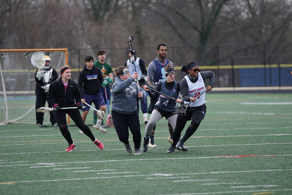 men and women playing lacrosse sport during daytime