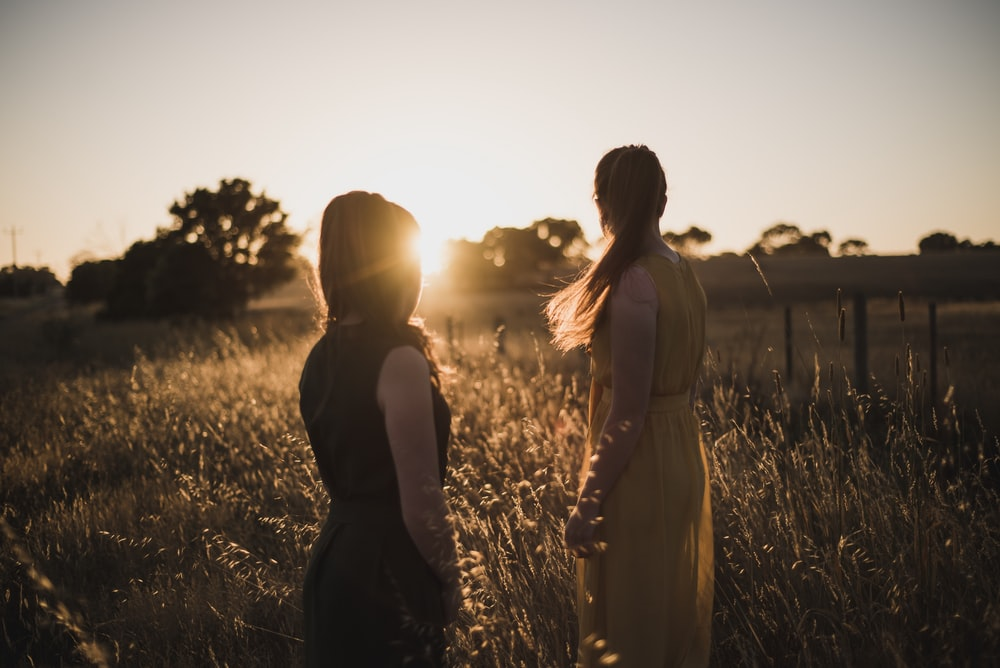 two women standing on grass field during golden hour