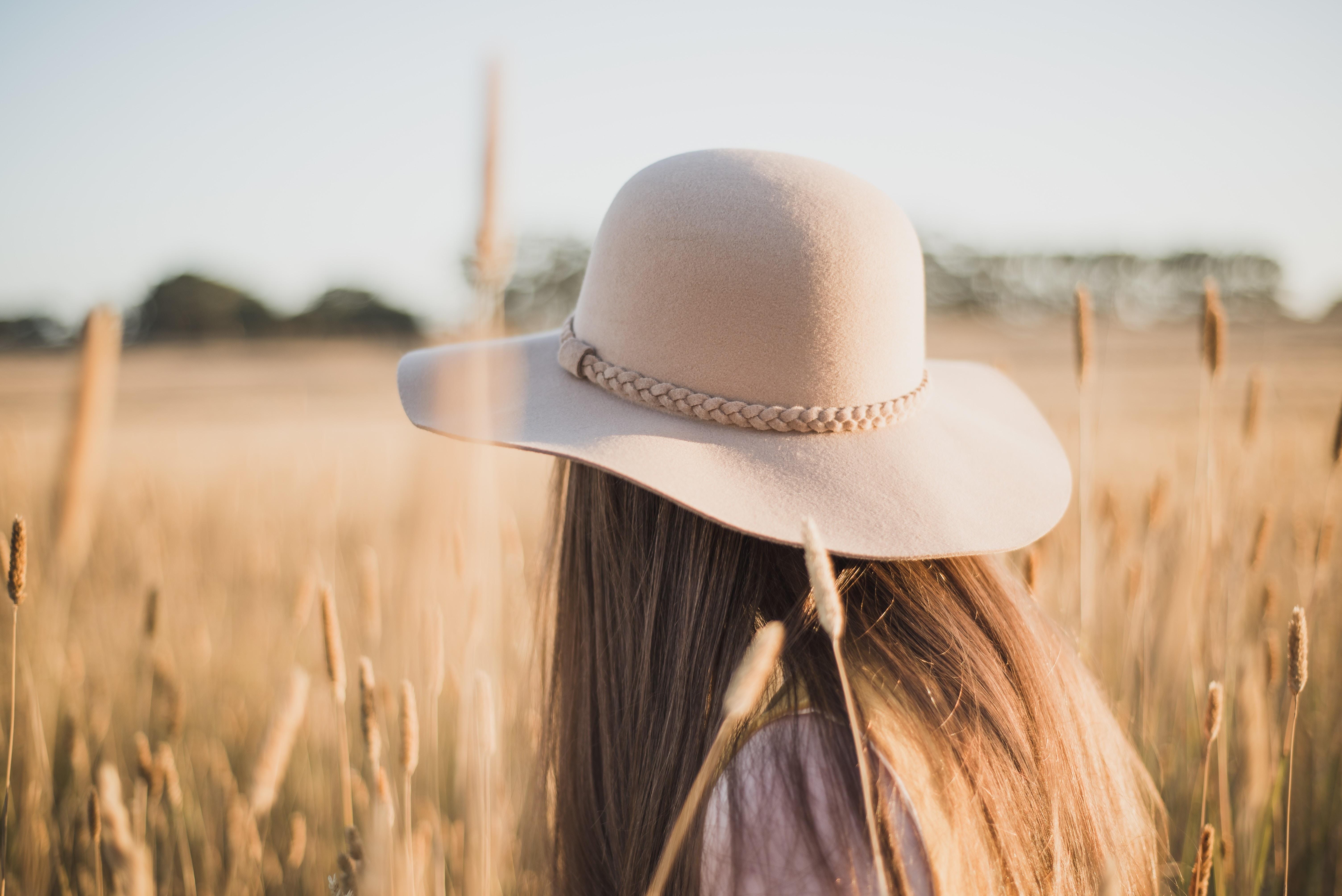 woman wearing beige sun hat standing on wheat field