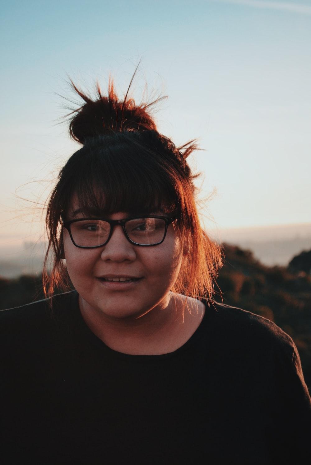 woman wearing eyeglasses smiling near mountains during daytime