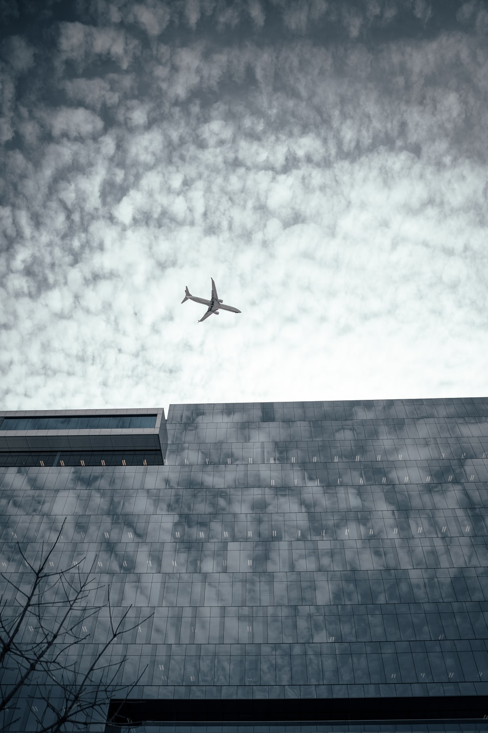 airliner on flight on top of gray high-rise building