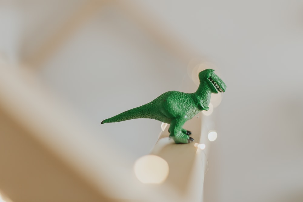 green T-rex toy on white stair