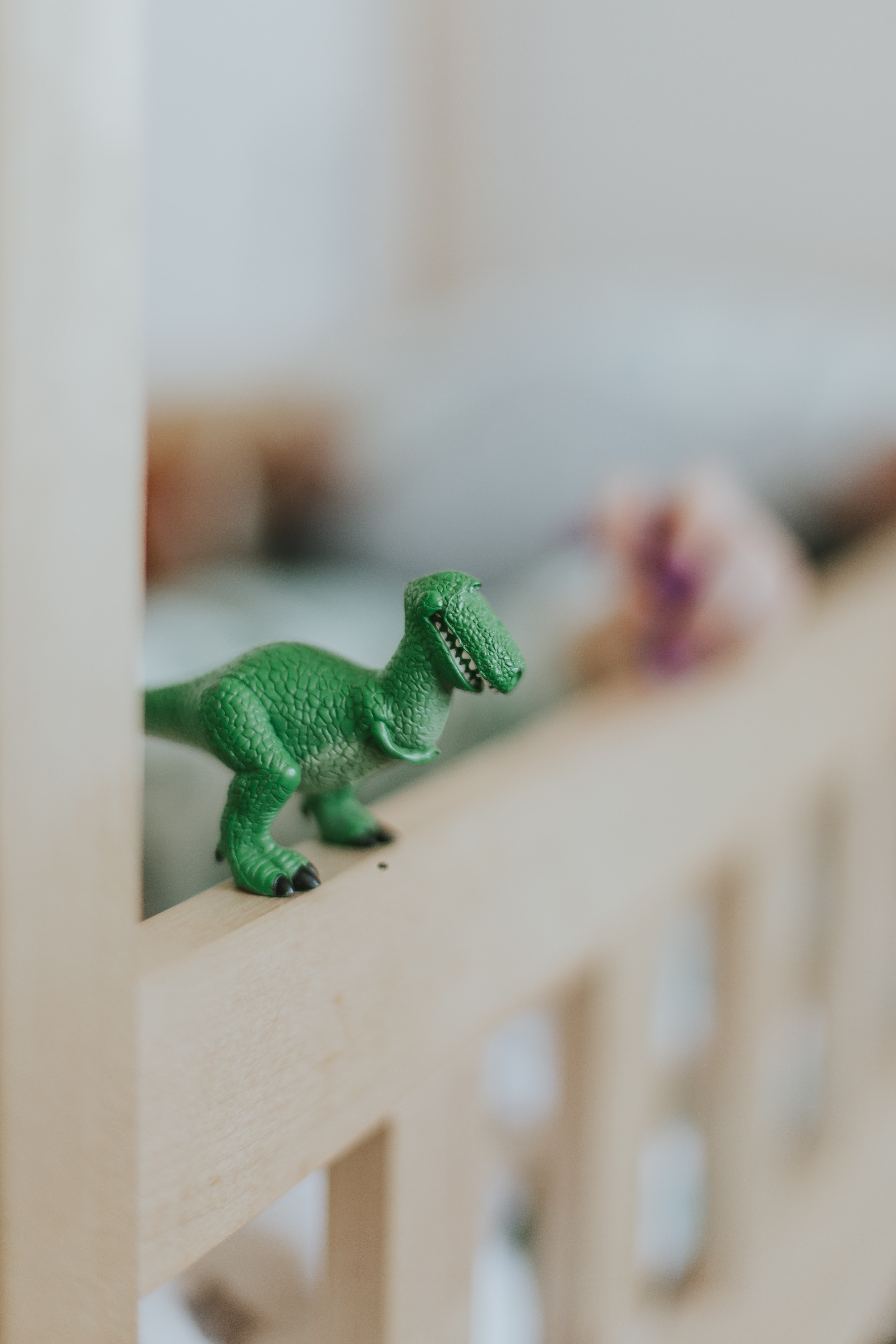 selective focus photography of green dinosaur scale model on brown wooden crib