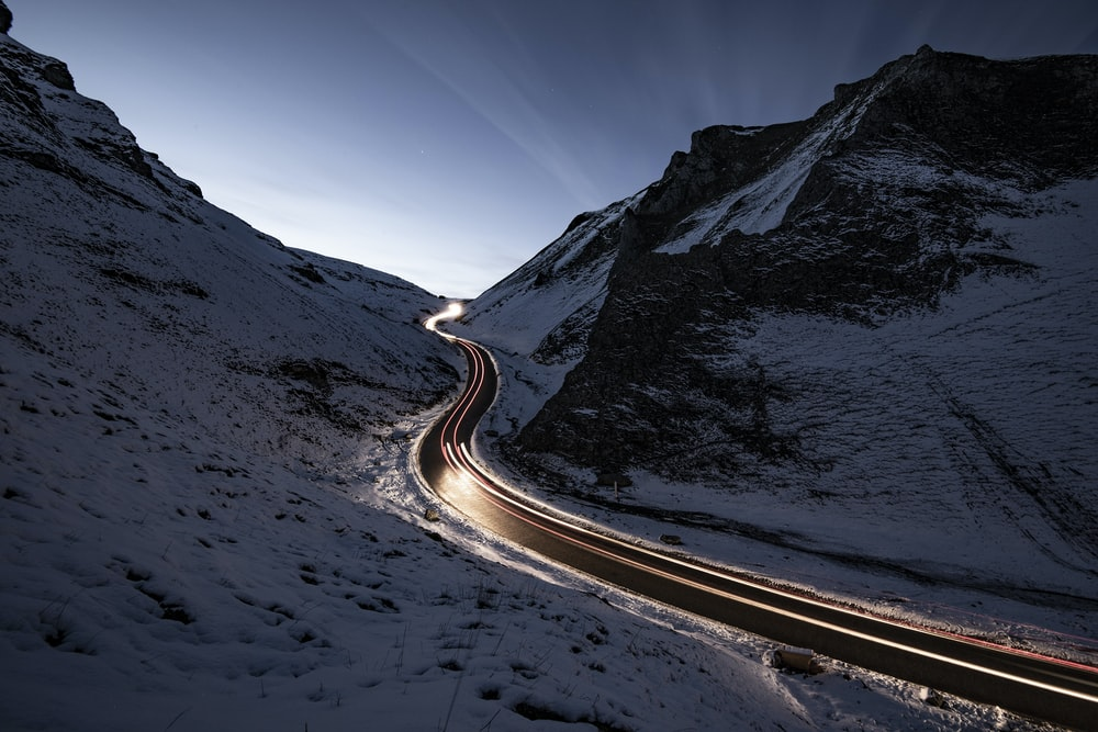 curvy road in middle of snow covered mountain