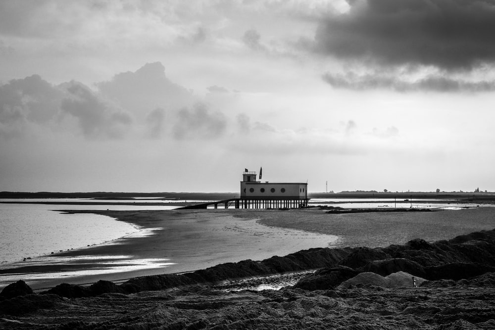 grayscale photography of lifeguard house at shore