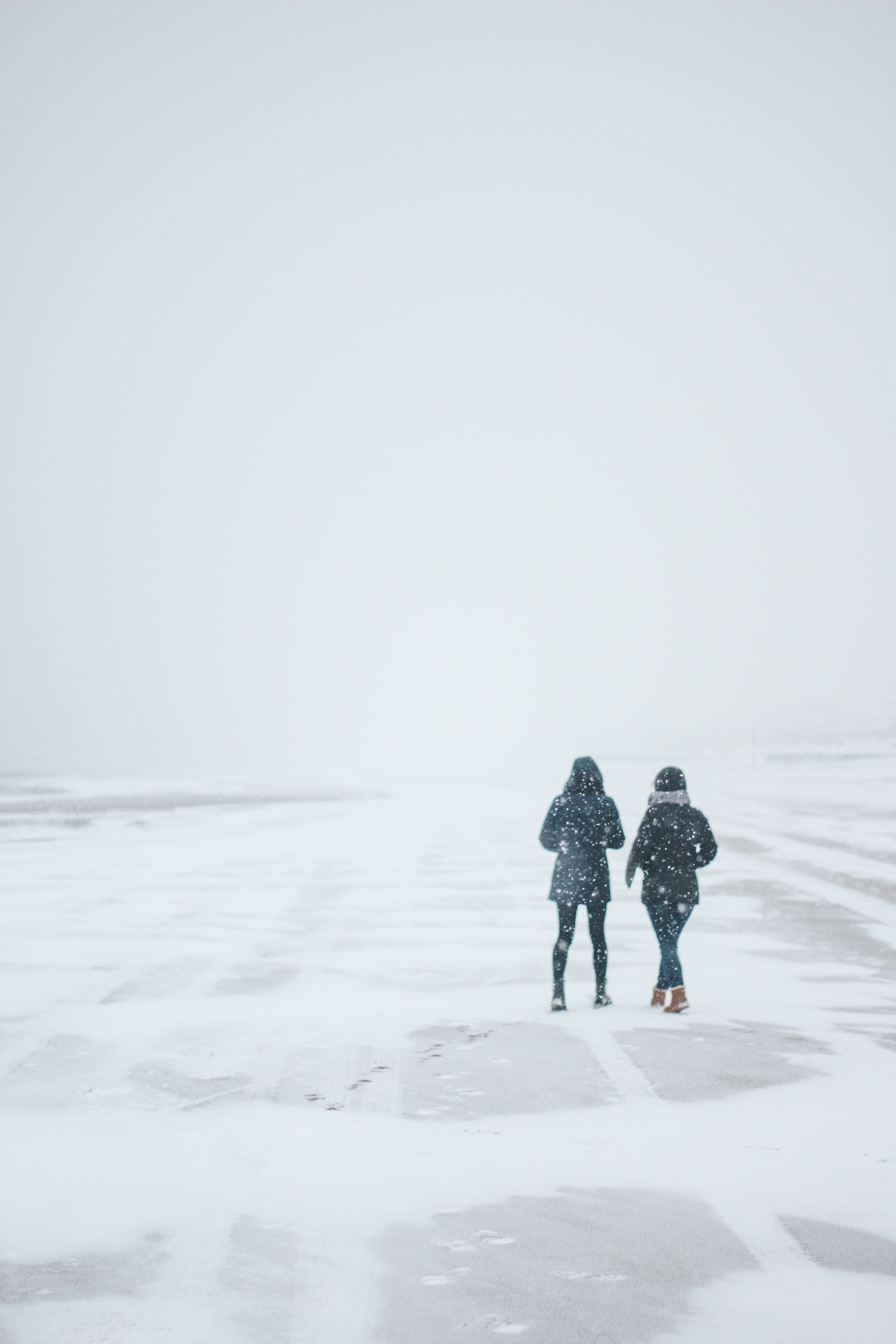 two persons walking on road path