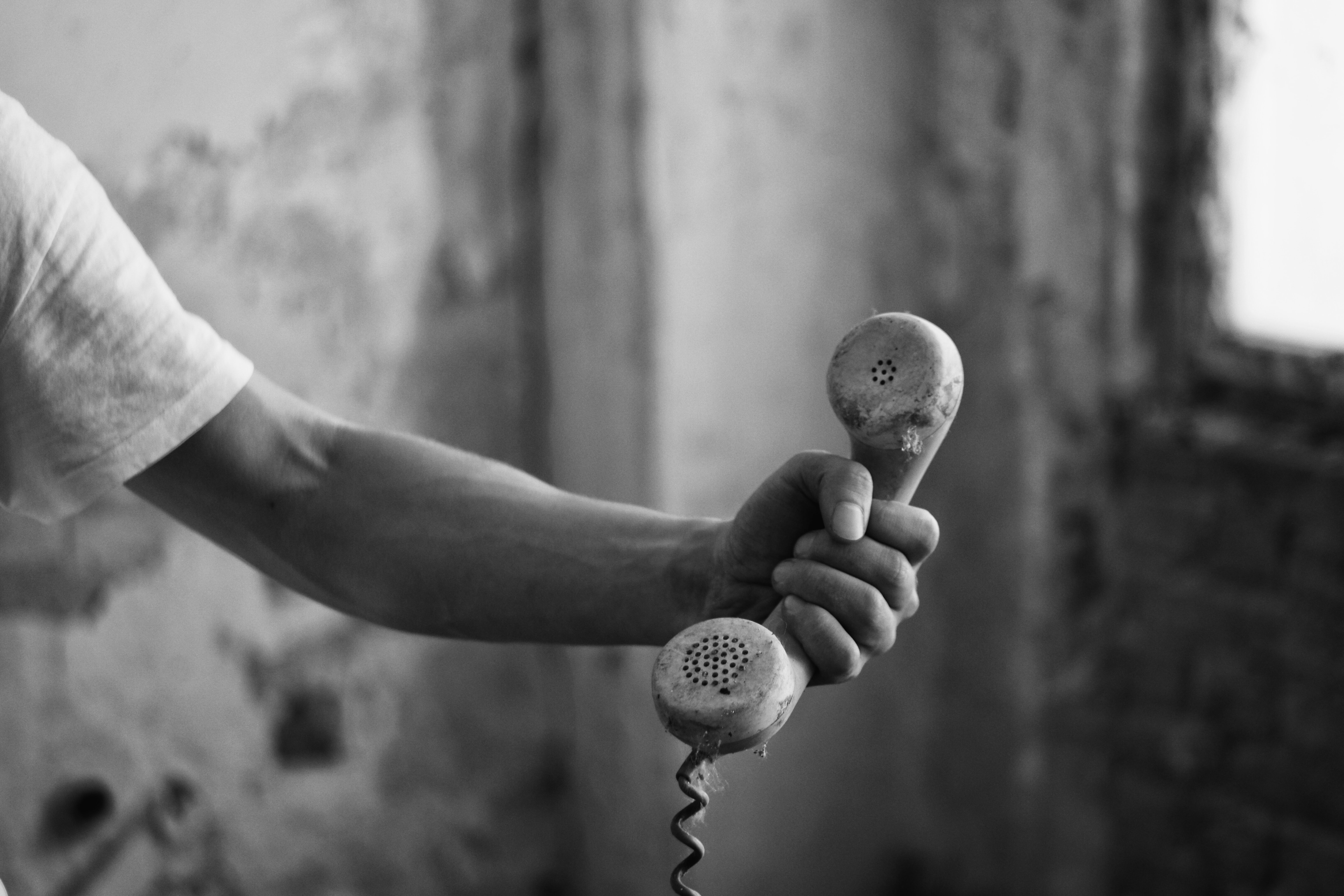 person holding telephone in grayscale phot