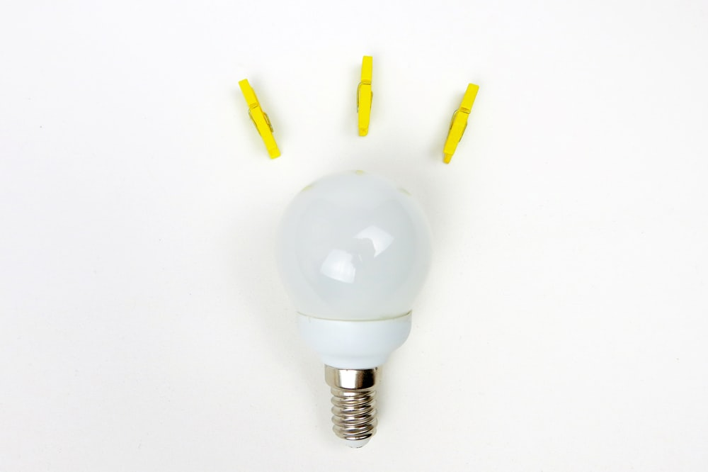 white light bulb near three yellow clips