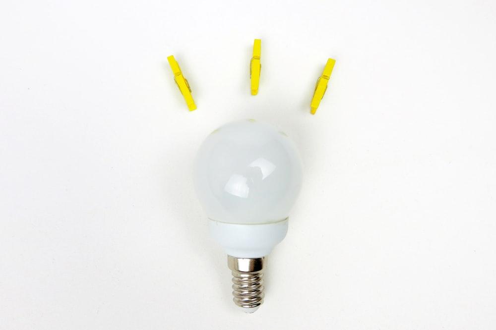 white light bulb near three yellow clips