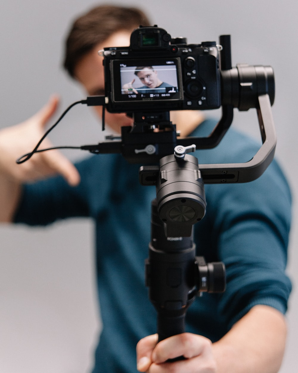 man holding black DSLR camera with stabilizer