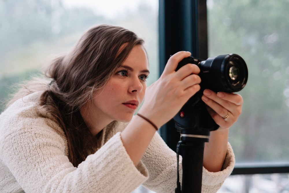 woman taking a photo using black DSLR camera