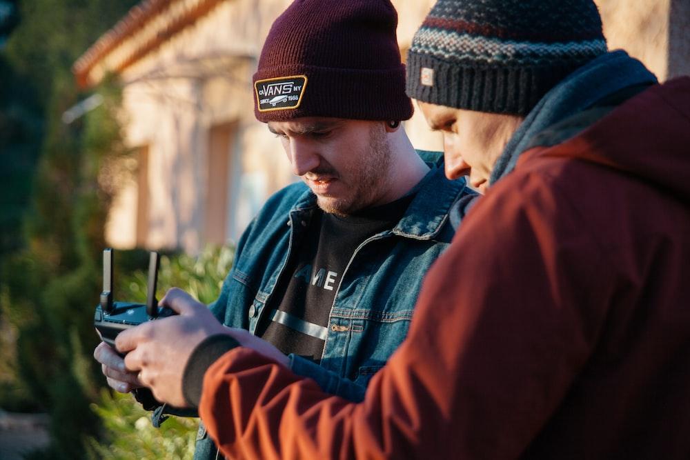 two men using black device