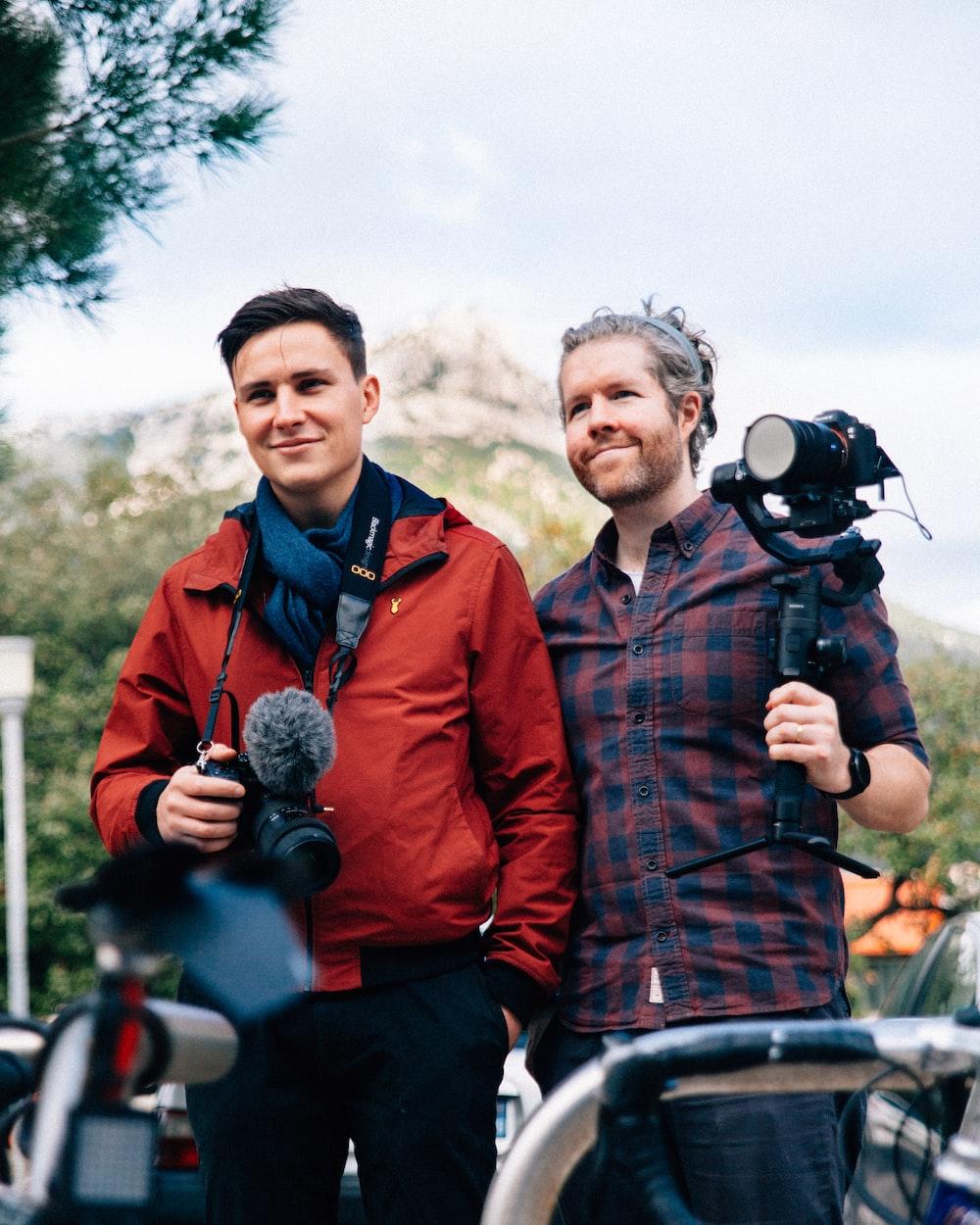 tow men holding cameras during daytime