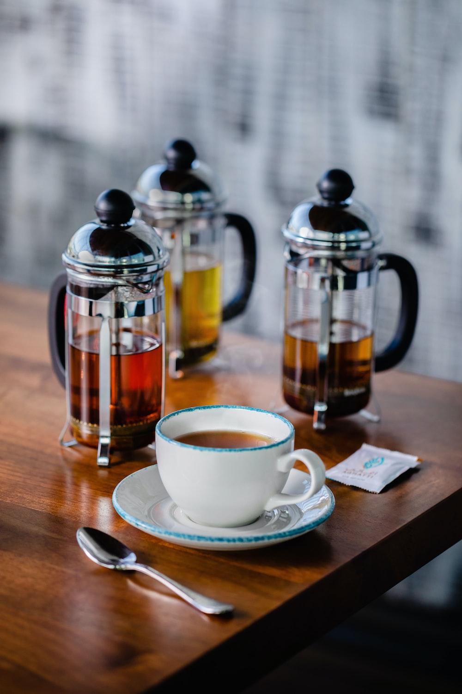 three coffee press and ceramic mug on table