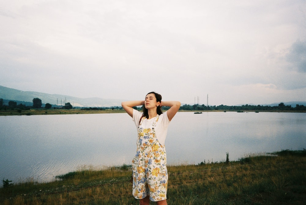 woman in floral dungaree holding hair while standing near lake