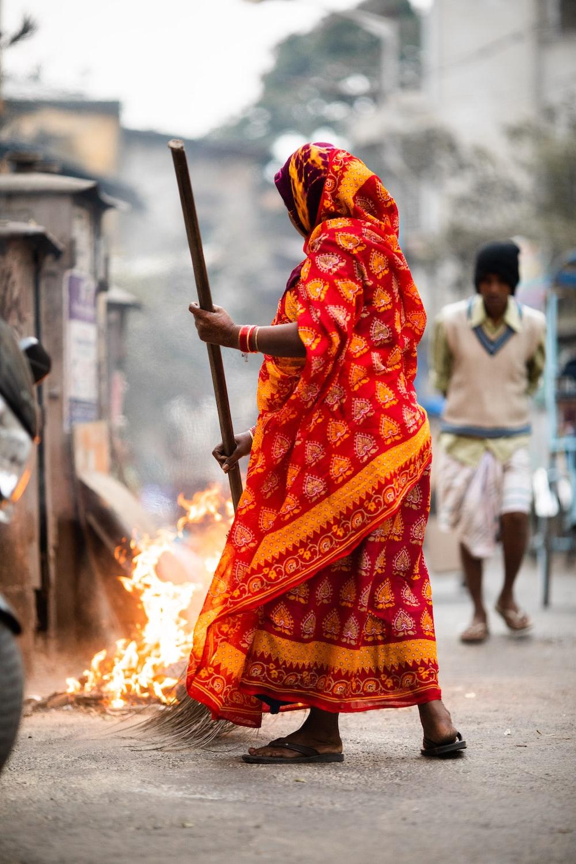 woman wearing orange dress holding broom