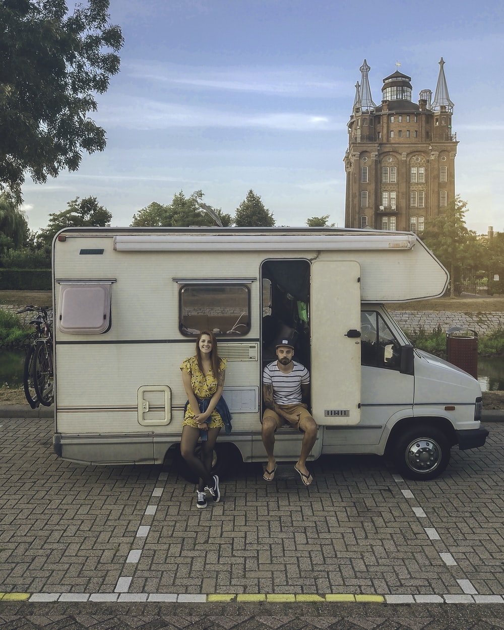 woman leaning and man sitting on RV