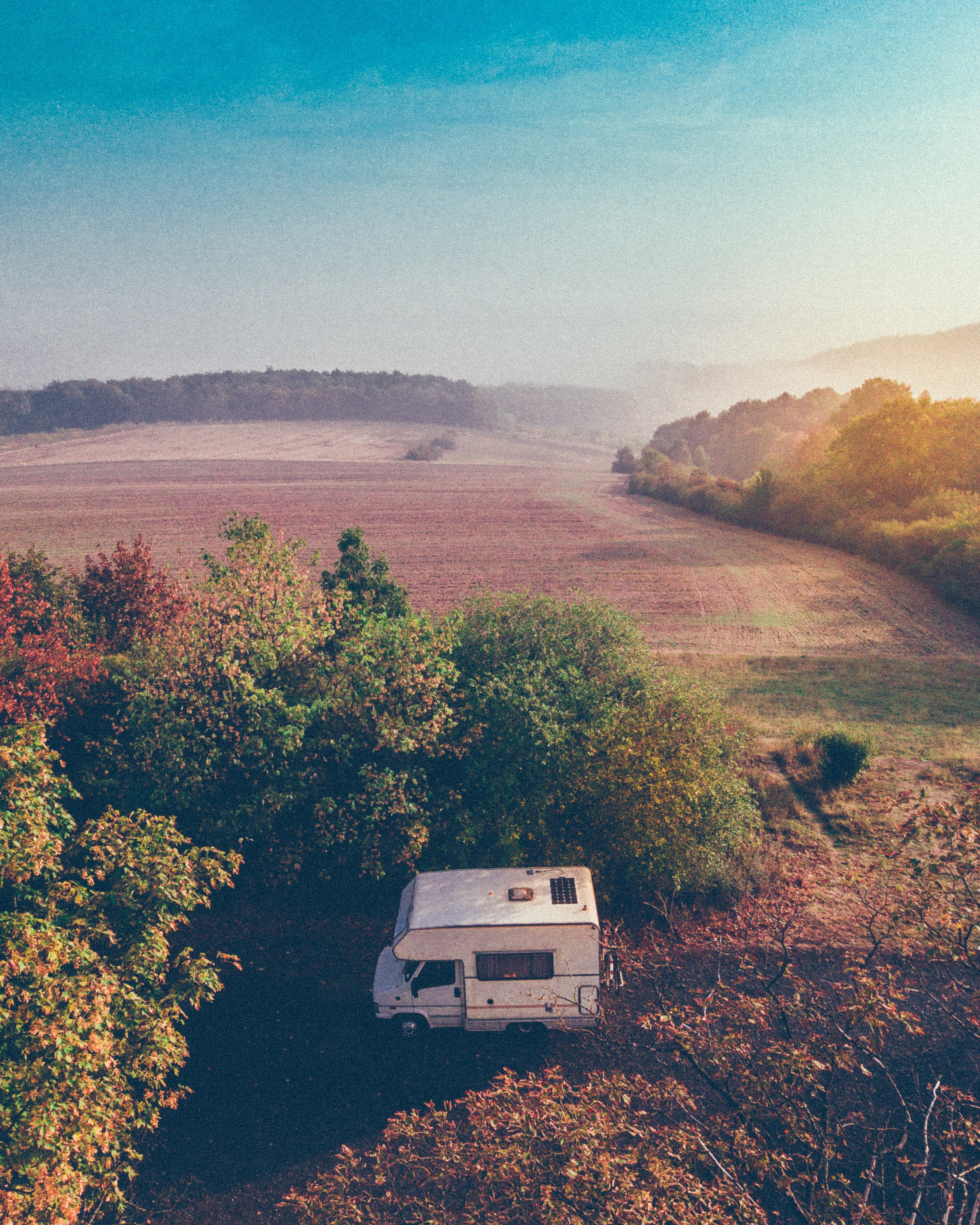 white camping van parked near trees