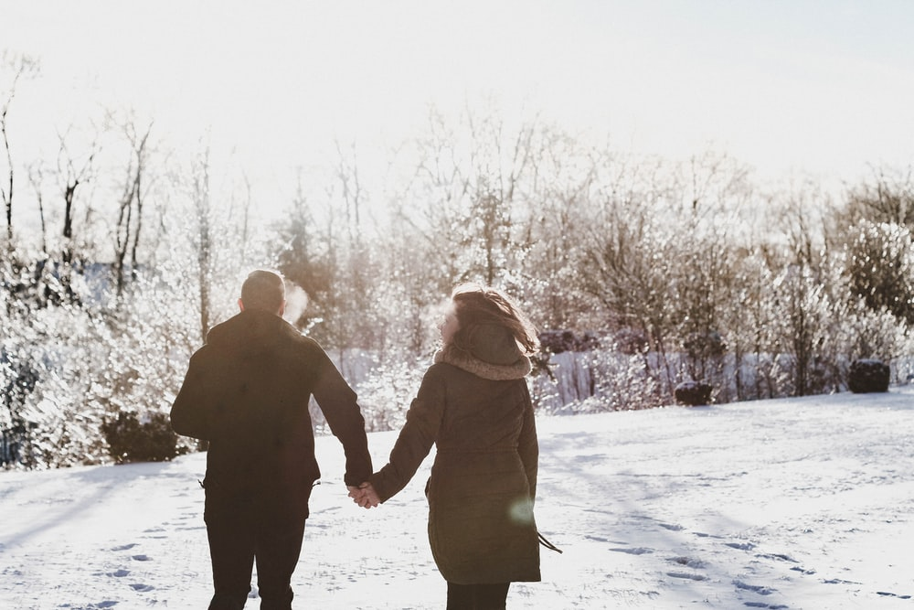 couple holding hand while walking on snow covered field