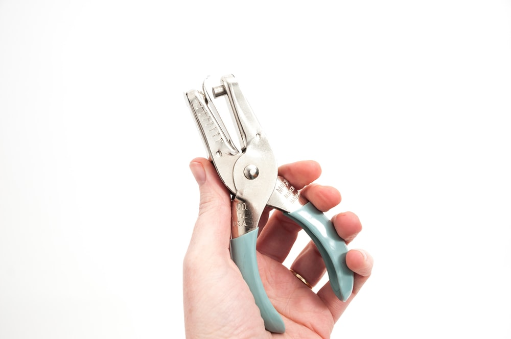 person holding gray cutting tools
