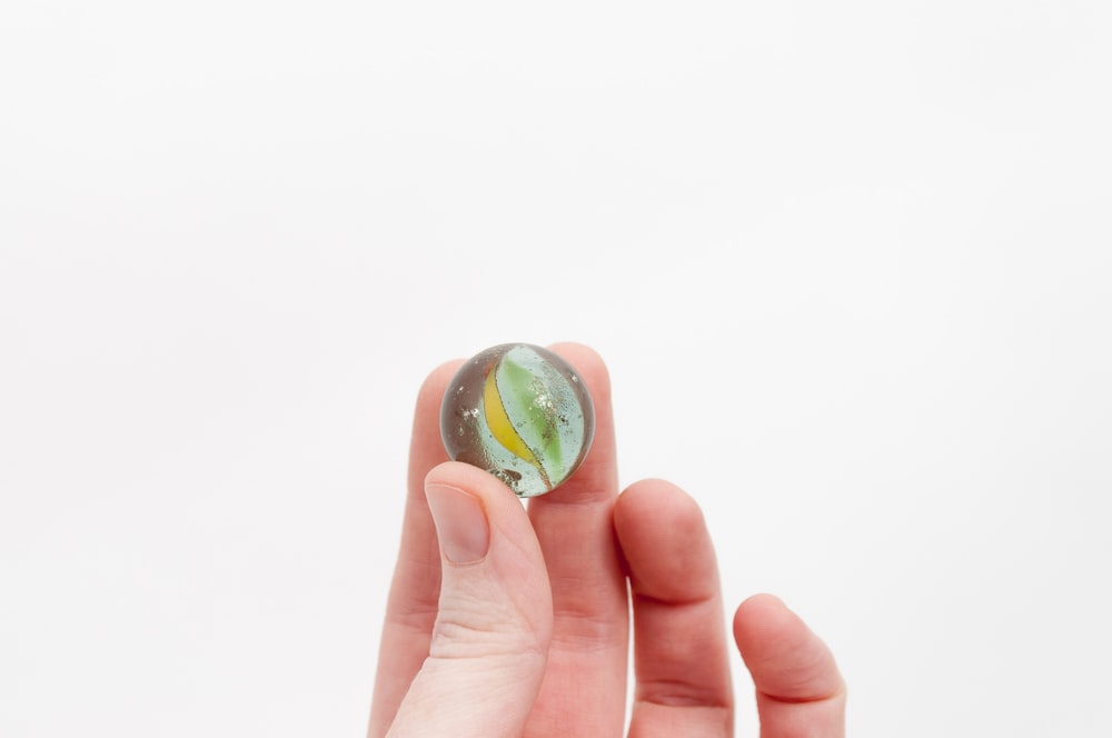 person holding yellow and green marble toy