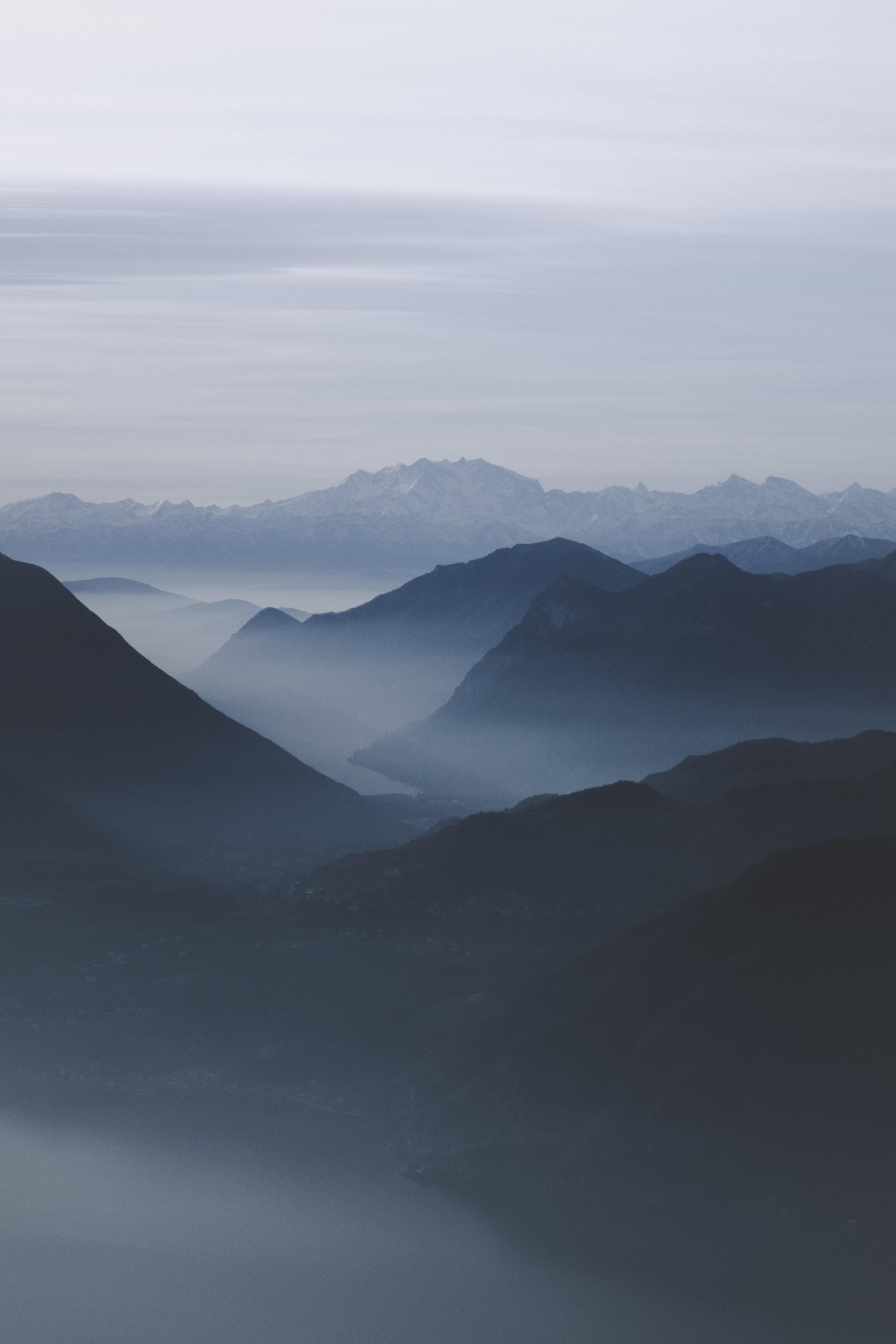 mist mountain range under white sky