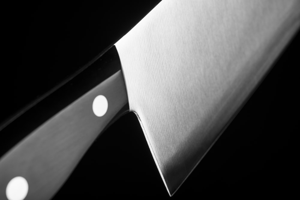 grayscale photo of gray cleaver with black handle