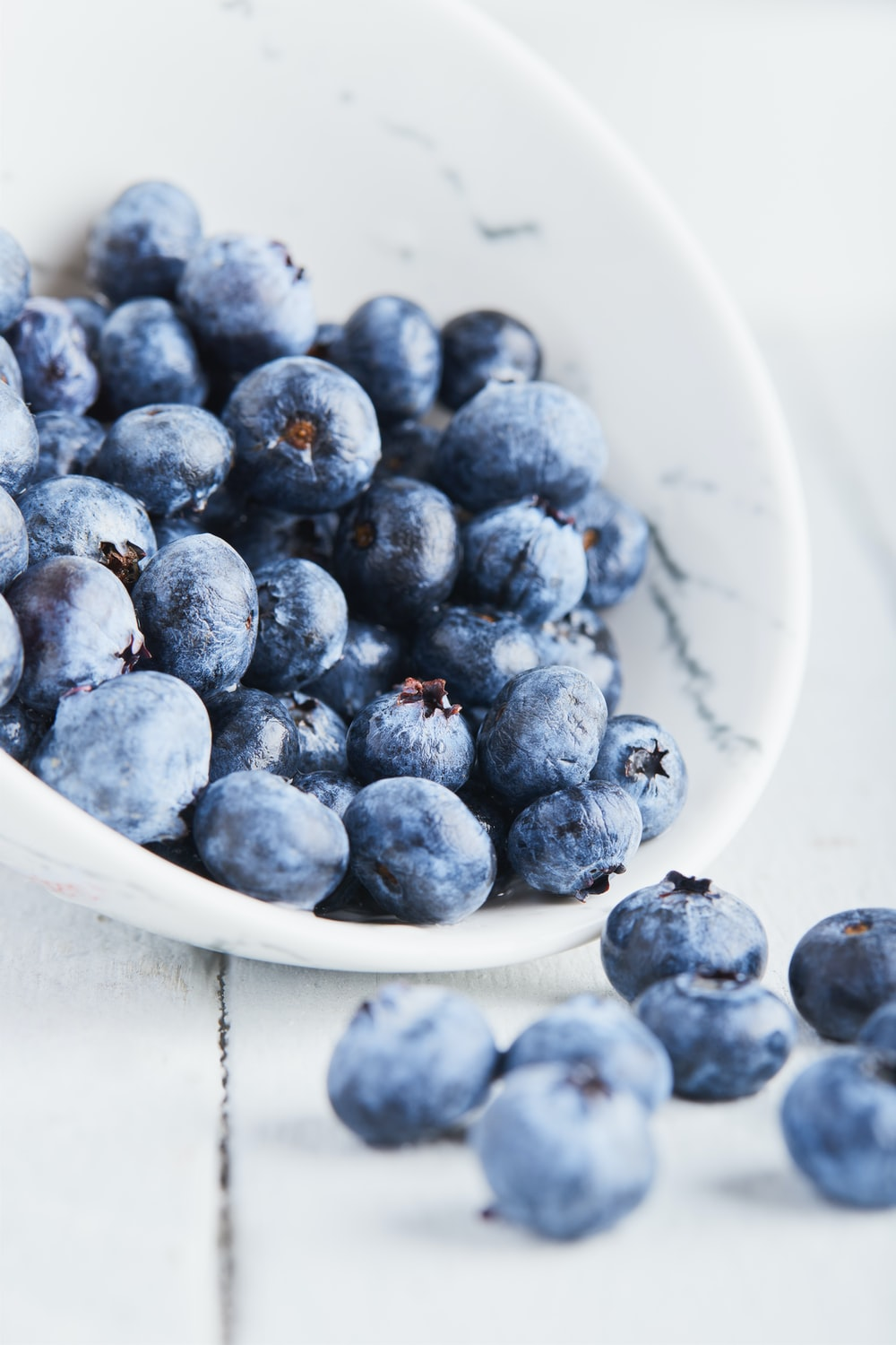 selective focus photography of blueberries in bowl