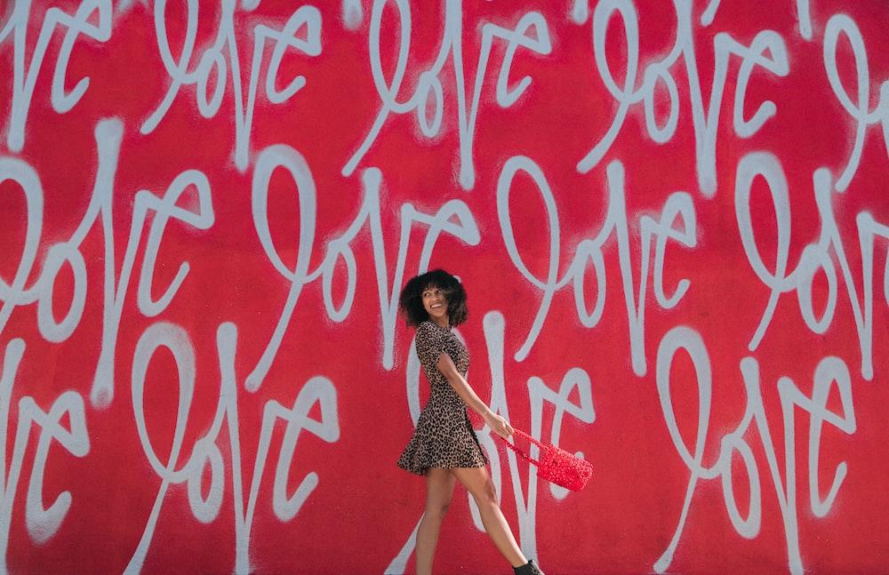 woman wearing brown-and-black mini dress standing near graffiti