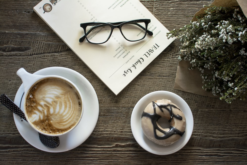 flatlay photo of latte with leaf art and doughnut