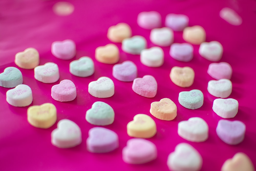 assorted-color heart candies on red textile