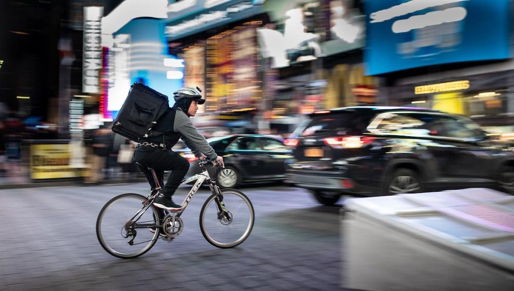 man riding bicycle near vehicles