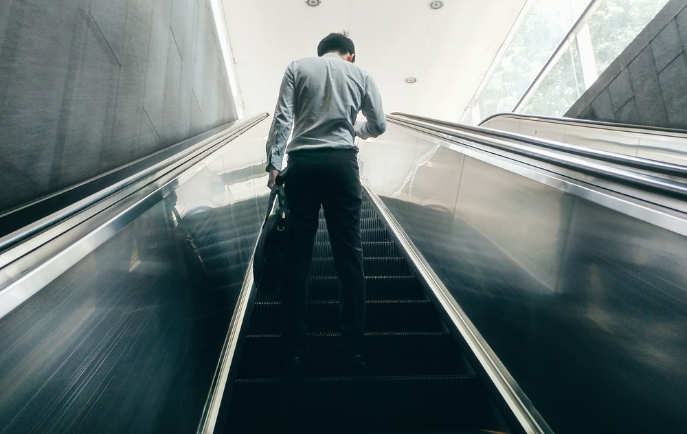 man standing on escalator