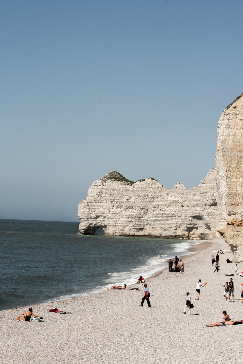 people on seashore near rock formation during daytime